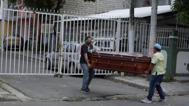 Dos mujeres en Guayaquil y de fondo el cuerpo de un hombre tapado en la calle.